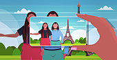 blogger using smartphone camera photographing african american travelers couple on mobile phone blogging shooting vlog concept paris abstract city silhouette background portrait horizontal