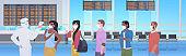 specialist in hazmat suit checking passengers temperature at airport terminal coronavirus pandemic