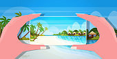 travel blogger using smartphone camera womens hands taking photo or video on mobile phone blogging shooting vlog concept sea beach summer vacation seascape background horizontal