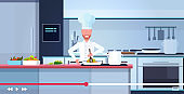 food blogger recording online video male chef in uniform cooking blogging concept man vlogger explaining how to cook a dish modern kitchen interior portrait horizontal