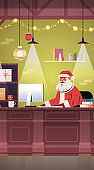 santa claus sitting at workplace and using computer merry christmas happy new year holidays celebration