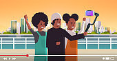 peope using selfie stick stabilizer african american travelers taking selfie photo on smartphone camera blogging shooting vlog concept modern cityscape background portrait horizontal