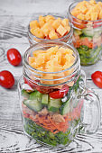 Layered salad with cheese, kale, carrot, chicken, cucumbers and cherry tomato