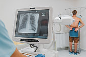 Young caucasian man standing against wall while doctor using X-Ray machine scan him in hospital