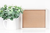Frame and flowers on the table. White colors. Greeting card. Background with copy space. Mock up.