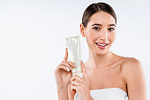 Beautiful caucasian young woman face portrait holding and presenting cream tube product