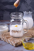 Honey is added into the jar with the ingredients for making porridge