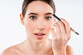 Close up studio shot of beautiful young woman applying makeup to her eyebrow while standing on isolated white background