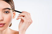 Studio shot of beautiful young woman having makeup on her eyebrow applying while standing at isolated white background