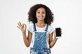 Little beautiful girl showing smarpthone screen over isolated white background doing ok sign with fingers