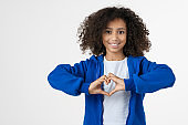 Young african girl kid showing heart love gesture isolated over white wall background