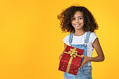 Little preteen african girl holding beautiful wrapped present isolated on background