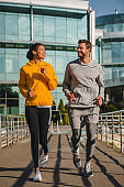 Vertical shot of a cheerful mixed race couple jogging outdoors in sportswear together