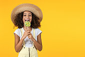 Cute young african girl kid eat candy isolated over yellow background