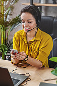 Vertical shot of female teleoperator working in home office with laptop and headset on while checking her smartphone