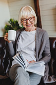 Vertical portrait of smiling mature woman reading book while relaxing on sofa at home with cup of coffee
