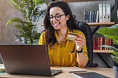 Young woman holding credit card and using laptop computer for online shopping