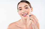 Young caucasian happy woman applying lip gloss isolated over white background