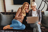 Senior woman and daughter using laptop and credit card for shopping online, having rest at home