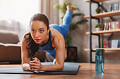 Fit young woman wearing sportswear working out at home on mat