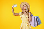 Amazing young woman posing isolated over yellow background holding shopping bags take selfie by mobile phone.