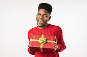 Cheerful african american man in casual wear with present box isolated on white background
