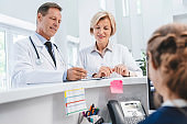 Two doctors colleagues standing at reception desk talking and sharing information with receptionist in modern clinic