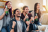 Happy friends and fans watching game on tv and celebrating victory at home