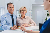 Young female receptionist with couple clients in hospital making payment via credit card