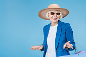 Senior woman shopper wearing sunglasses and hat with shop bags isolated on blue background