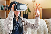 Woman touching something using virtual reality headset glasses and sitting on the couch at home
