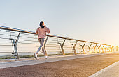 Healthy lifestyle concept. Back view of athletic woman running on city bridge. Morning jogging.