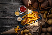 French fries potatoes on a rustic wooden board table with raw potatoes around