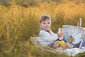 Boy kid with milk and fruit on a picnic in sunny day Autumn is a great and beautiful picnic time.