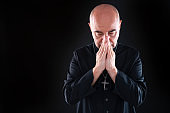 Bald priest praying with hands on black