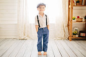 Cute boy in a white shirt, cap and suspenders in a bright room. Retro style in clothes