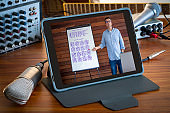 Music e-learning teleconference teacher in digital tablet PC screen on wood table