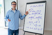 Maths teacher man teaching on white board pointing equation from home