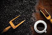 Black coffee beans dark roast, scoop with ground coffee, coffee cup