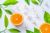 Azahar flower orange blossom and half cut orange fruit on white