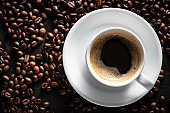 Black Coffee cup on rustic wood and coffee beans background