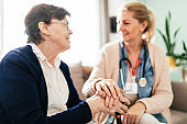 Senior woman and nurse holding hands during home care visit