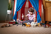 Girl making hideout at home, using headphones to listen kids' music from smart phone
