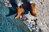 Unrecognizable woman in yellow trekking boots sits on coast near of turquoise water, top view. Adventure, scout, discovery, explorer concept