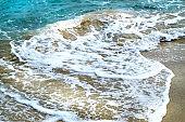 White foam of a blue sea tropical wave on the Golden sand of the beach in Palma de Mallorca