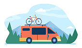 Minivan with bike on top moving in mountain