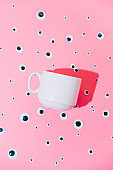 White cup or mug lays among cartoon toy eyes on a pink pastel surreal background. Breakfast minimalism