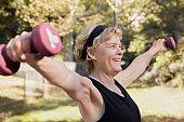 Mature woman exercising using dumbbells