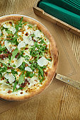 Tasty pizza with cheese, wild mushrooms, chanterelles arugula and parmesan on a wooden background. Italian traditional cuisine. Top view. Food for lunch