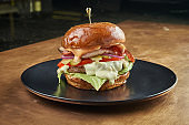 Appetizing and juicy burger with pork. tomato, onion, lettuce, bacon and melted cheese in a dark ceramic plate on a copper, metal background